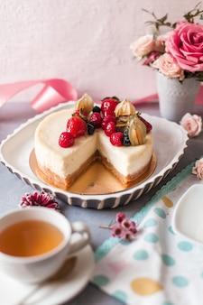 Colpo estetico di una cheesecake con frutti di bosco disposti con fiori