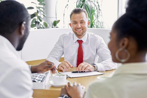 Affabile venditore professionista caucasico mostra il documento ai clienti