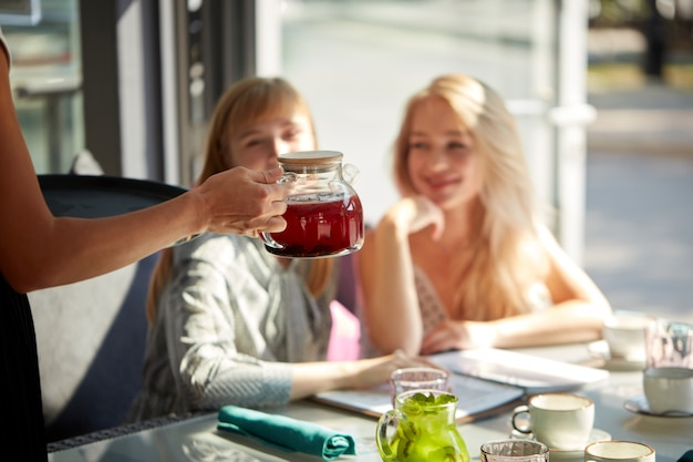 L'affabile cameriere del bar offre bevande dolci a due bellissime clienti femminili sedute nel loro ristorante