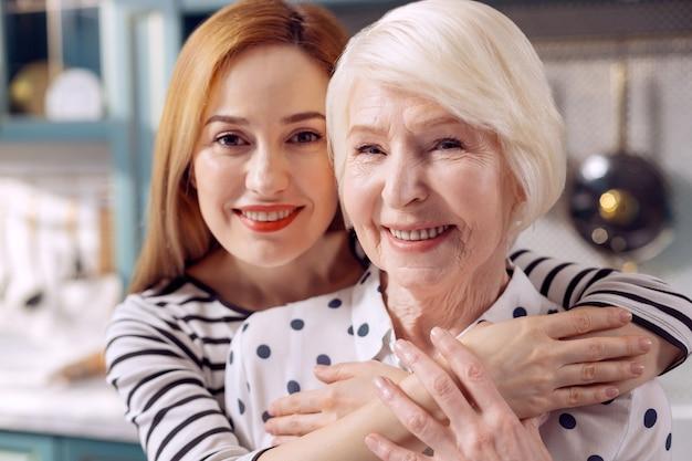 Legame affettuoso. il primo piano di una giovane donna felice che lega alla sua anziana madre e posa per la telecamera mentre le dà un abbraccio
