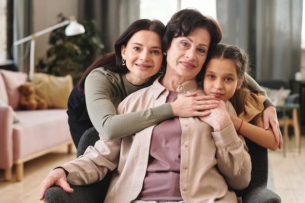 Femmine affettuose di tre generazioni in piedi davanti alla telecamera