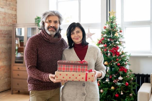 Affettuosa coppia matura in abbigliamento casual che tiene scatole regalo con regali per i loro nipoti contro l'albero di natale decorato in soggiorno