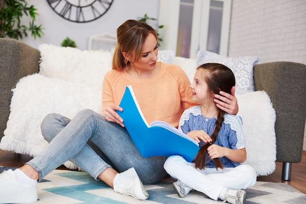 Mamma affettuosa che aiuta sua figlia a fare i compiti