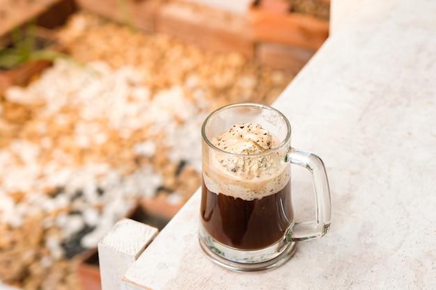 Caffè affogato con gelato su una tazza di vetro con sfondo giardino, cocktail estivo (primo piano, fuoco selettivo)