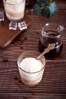 Caffè affogato con gelato in un bicchiere sul tavolo di legno.