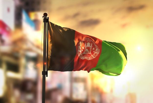 Bandiera dell'afghanistan contro la città sfocata di sfondo al retroilluminazione di alba