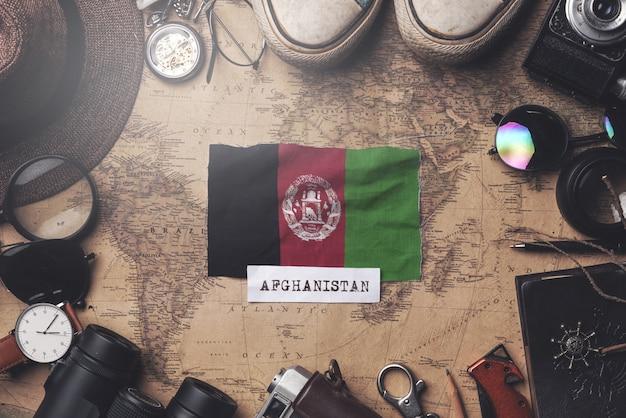 Bandiera afghanistan tra gli accessori del viaggiatore sulla vecchia mappa vintage. colpo ambientale