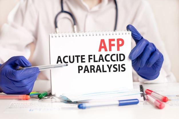 Carta di afp nelle mani del medico. mani del medico in guanti blu che tengono un foglio di carta con testo afp - abbreviazione di paralisi flaccida acuta, concetto medico.