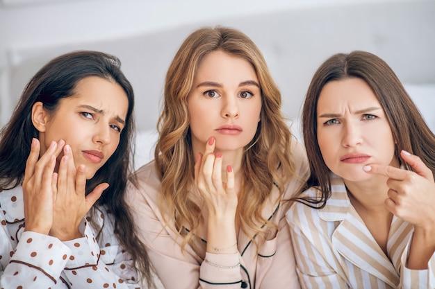 Paura dell'invecchiamento. tre ragazze che toccano la loro pelle che sembrano insoddisfatte