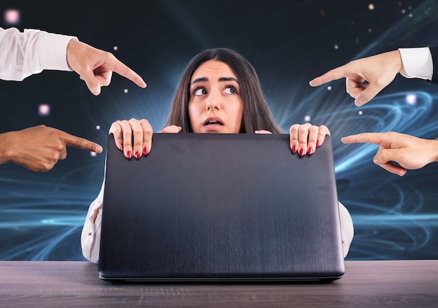 La ragazza impaurita si nasconde dietro il laptop. è vittima di cyberbullismo