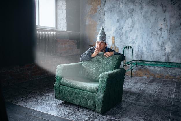 Uomo impaurito in berretto di alluminio guarda la tv, protezione della mente, concetto di paranoia. ufo, teoria del complotto, fobia della telepatia