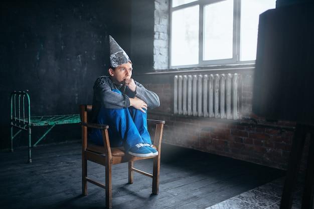 Uomo impaurito in casco di carta stagnola guarda la tv, concetto di paranoia. ufo, teoria del complotto, protezione dal furto di cervello, fobia