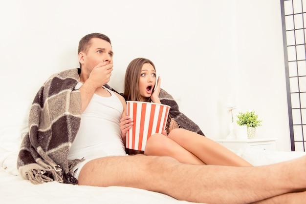Uomo impaurito e donna che guardano film horror con popcorn prima di dormire