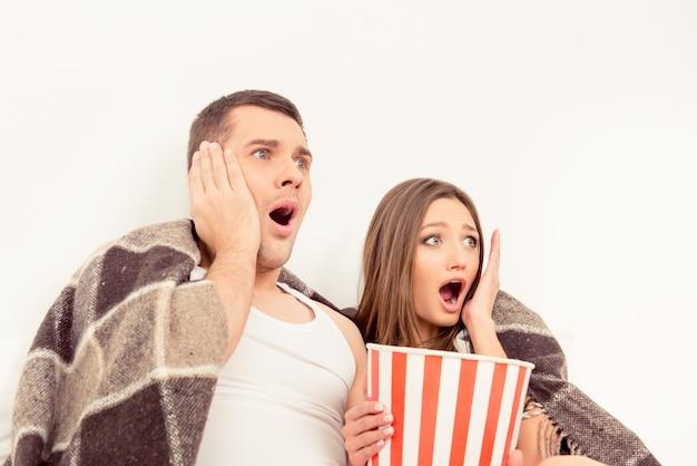 Uomo impaurito e donna che guardano film horror con popcorn