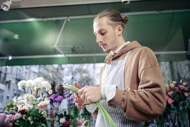 Non avere paura. uomo serio che tiene i fiori nella mano sinistra durante il taglio dei gambi