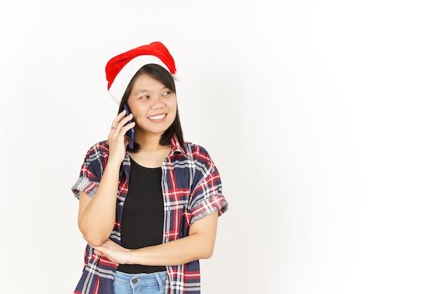 Paura e parlando al telefono bella donna asiatica che indossa una camicia scozzese rossa e un cappello da babbo natale