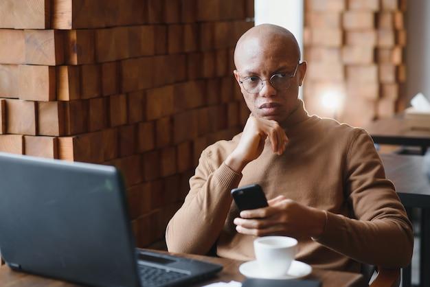 Imprenditore afro-americano che indossa una camicia con maniche arrotolate guardando attraverso la finestra con un'espressione del viso premurosa e seria, sentendosi nervoso prima di incontrare i partner commerciali al bar