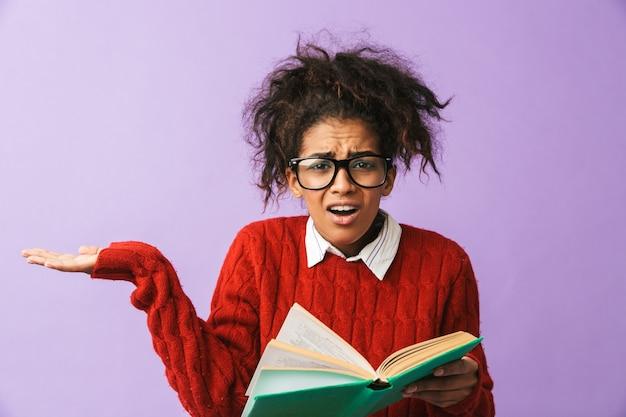 Ragazza adorabile dell'afroamericano in uniforme scolastica che tiene e libro di lettura, isolato