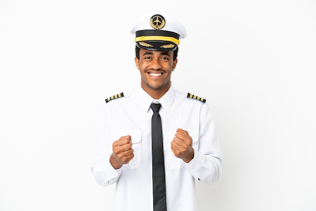 Pilota di aeroplano afroamericano sopra fondo bianco isolato che celebra una vittoria nella posizione del vincitore