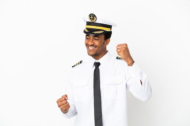 Pilota di aeroplano afroamericano sopra fondo bianco isolato che celebra una vittoria