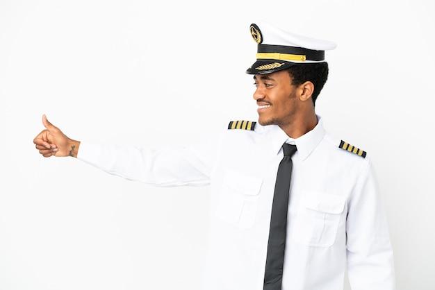 Pilota di aeroplano afroamericano sopra fondo bianco isolato che dà un gesto di pollice in alto