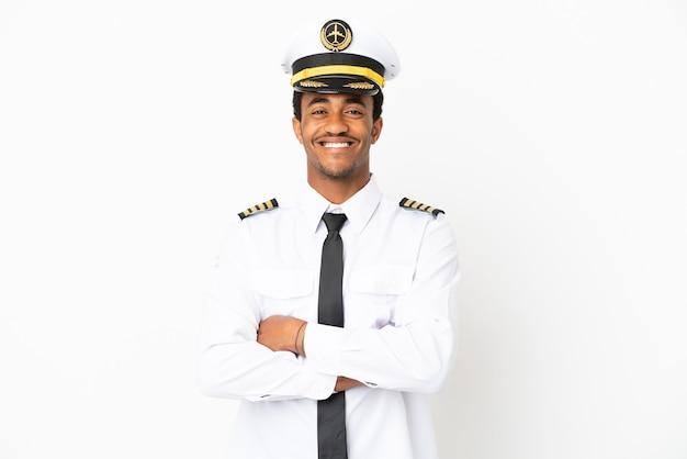 Pilota di aeroplano afroamericano su sfondo bianco isolato mantenendo le braccia incrociate in posizione frontale
