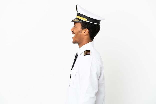 Pilota di aeroplano afroamericano su sfondo bianco isolato ridendo in posizione laterale