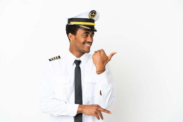 Pilota di aeroplano afroamericano su sfondo bianco isolato rivolto verso il lato per presentare un prodotto