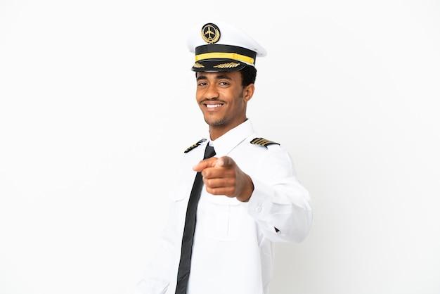 Il pilota di aeroplano afroamericano su sfondo bianco isolato punta il dito contro di te con un'espressione sicura