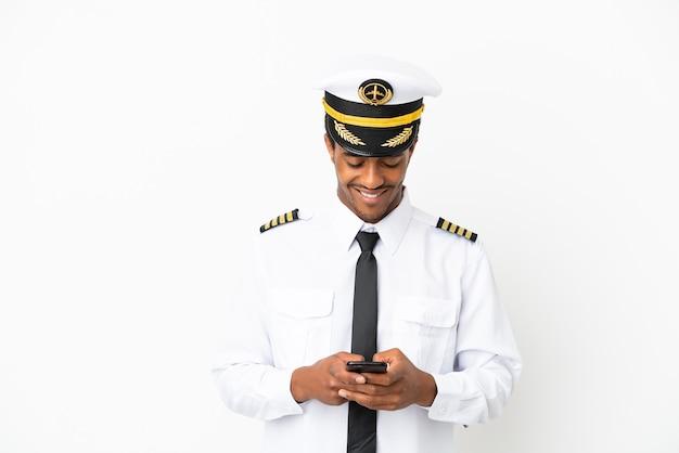 Pilota di aeroplano afroamericano su sfondo bianco isolato inviando un messaggio con il cellulare