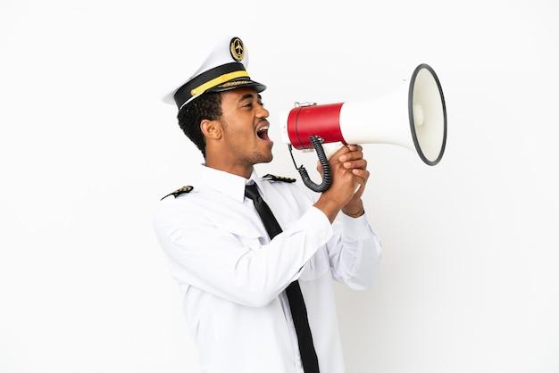 Pilota di aeroplano afroamericano su sfondo bianco isolato che grida attraverso un megafono