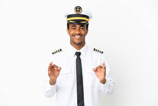 Pilota di aeroplano afroamericano su sfondo bianco isolato che mostra un segno ok con le dita