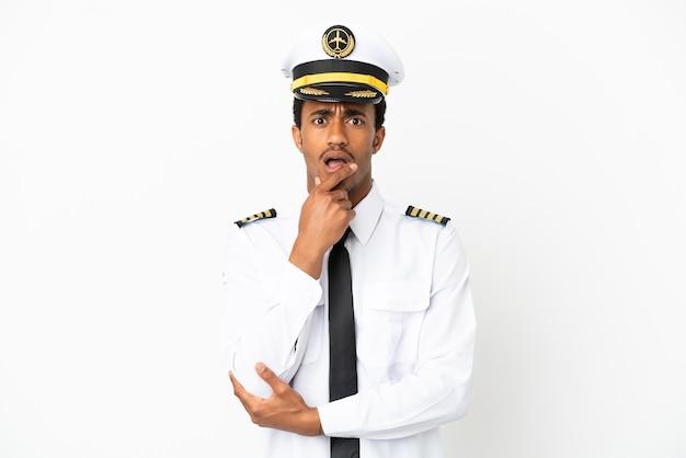 Pilota di aeroplano afroamericano su sfondo bianco isolato sorpreso e scioccato mentre guardava a destra