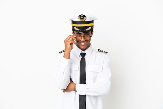 Pilota di aeroplano afroamericano sopra fondo bianco isolato con gli occhiali e felice