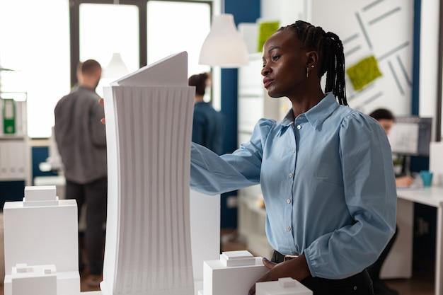 Architetto afroamericano costruttore in ufficio che lavora al piano del modello di edificio