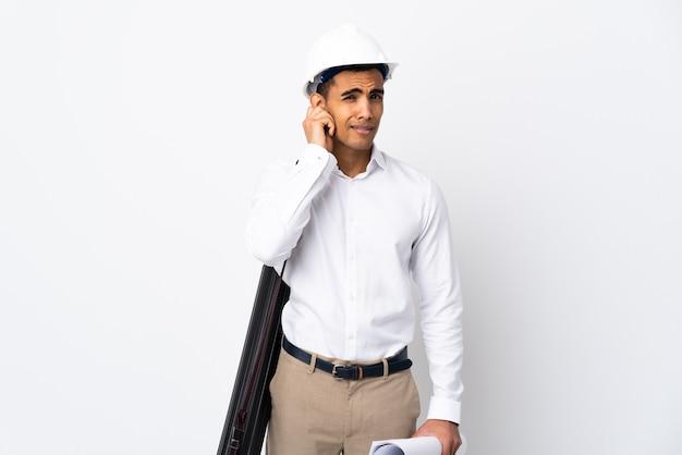 Uomo afroamericano dell'architetto con il casco e le cianografie della tenuta sopra le orecchie frustrate e della copertura isolate del _ del fondo bianco