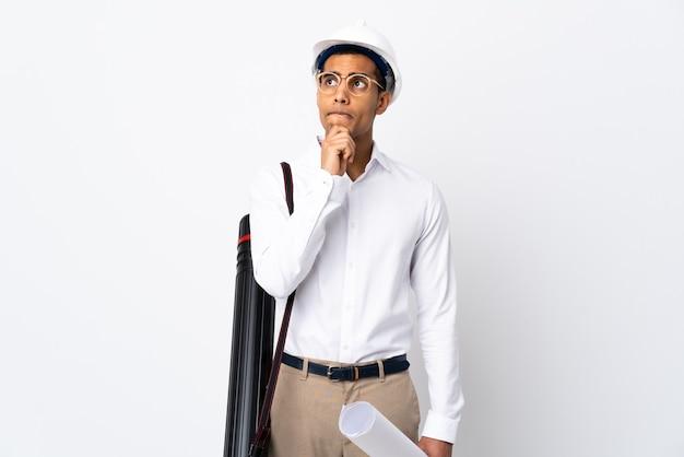 Uomo afroamericano dell'architetto con il casco e che tiene le cianografie sopra fondo bianco isolato _ che ha dubbi e pensiero