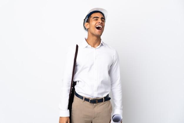 Uomo afroamericano dell'architetto con il casco e che tiene i modelli sopra la risata bianca isolata del _