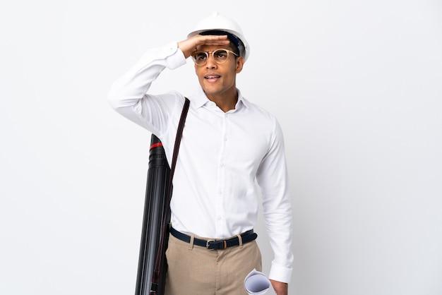 Uomo afroamericano dell'architetto con il casco e che tiene le cianografie sopra il _ del fondo bianco isolato che guarda lontano con la mano per guardare qualcosa