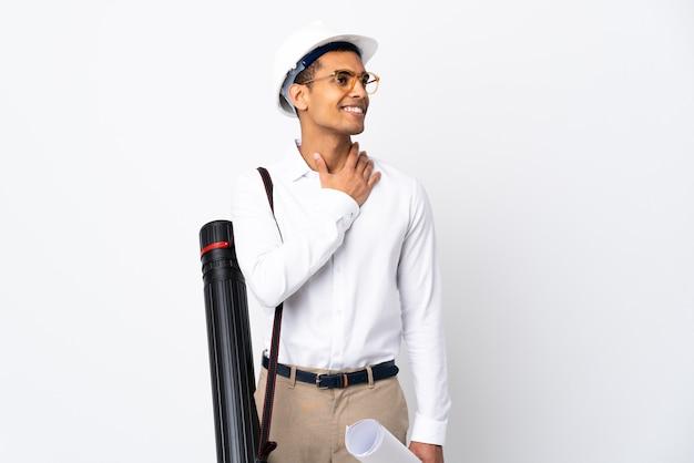 Uomo afroamericano dell'architetto con il casco e che tiene i modelli sopra fondo bianco isolato _ che osserva in su mentre sorride