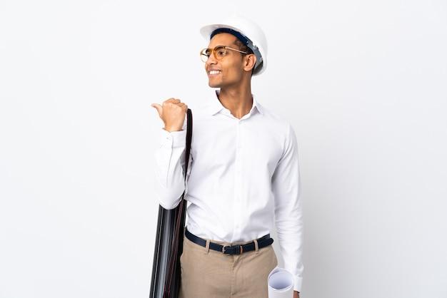 Uomo afroamericano dell'architetto con il casco e che tiene i modelli sopra il _ bianco isolato del fondo che indica al lato per presentare un prodotto
