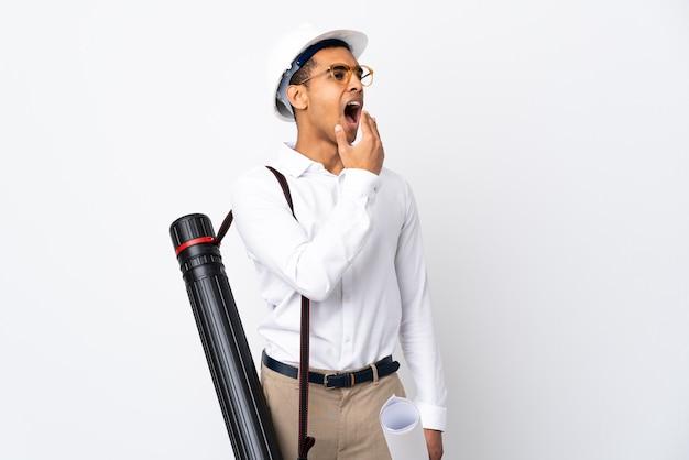 Uomo afroamericano dell'architetto con il casco e che tiene i modelli sopra il _ bianco isolato che sbadiglia e che copre la bocca spalancata con la mano