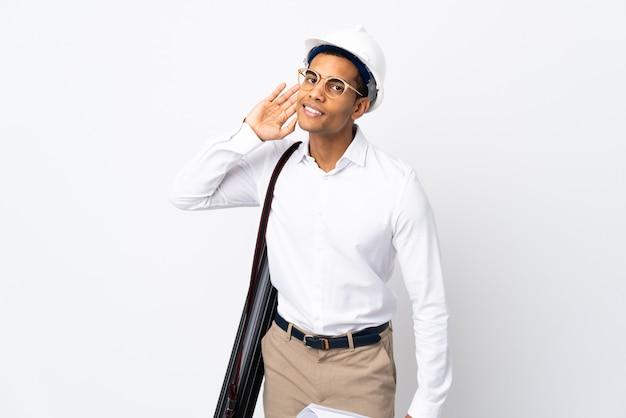 Uomo dell'architetto afroamericano con il casco e tenere i modelli sopra la parete bianca isolata _ ascoltando qualcosa mettendo la mano sull'orecchio