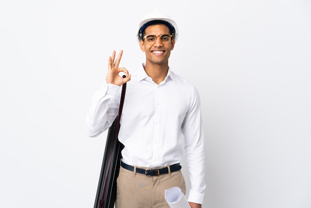 Uomo dell'architetto afroamericano con il casco e i modelli della tenuta sopra la parete bianca isolata _ che mostra segno giusto con due mani