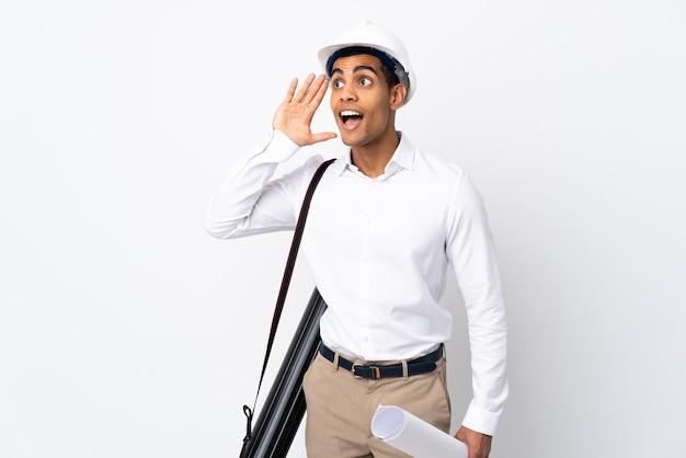 Uomo afroamericano dell'architetto con il casco e che tiene i modelli su bianco isolato