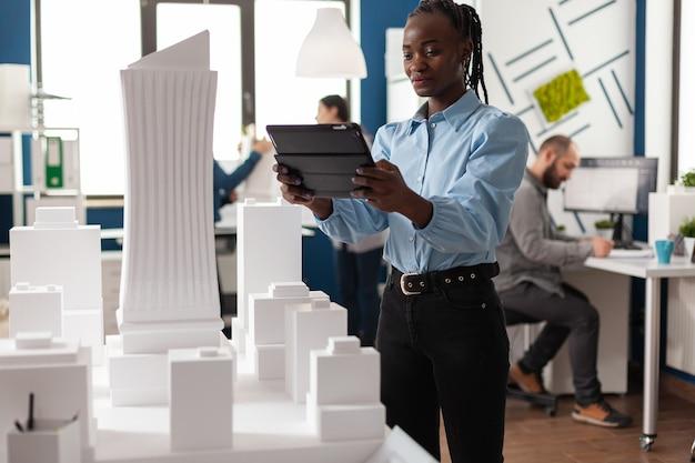Architetto afroamericano donna che lavora su tablet guardando edificio maquette