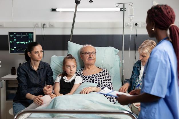 Assistente afroamericano che monitora uomo anziano anziano durante il recupero clinico