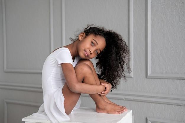 La ballerina afroamericana in un costume da ginnastica bianco si siede su una sedia di legno
