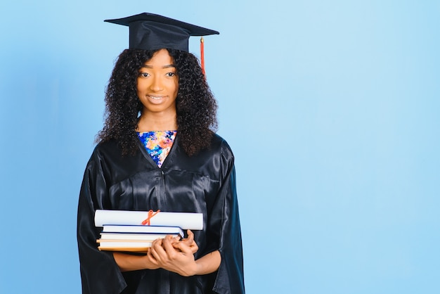 Bella donna afro-americana in una veste nera e cappello, su uno sfondo blu isolato sorride.
