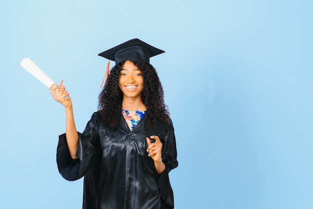 Bella donna afro-americana in una veste nera e un cappello, su uno sfondo blu isolato sorride.